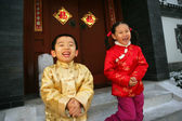 Two children(5-36 years) standing in front of chinese traditiona — Stock Photo