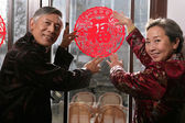 Chinese mature couple holding chinese cut paper on New year's Ev — Stock Photo