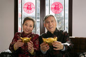 Chinese mature couple making a wish with hands holding bars of g — Stock Photo