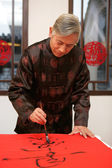 Chinese mature man writing Chinese couplet — Stock Photo