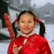 One chinese girl holding a sugar-coated haws thinking — Stock Photo