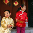 Two children(5-20 years) standing in front of chinese traditiona — Stock Photo