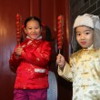 Two chinese children dressed in traditional clothing raising can — Stock Photo #34911539