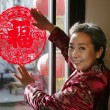 Stock Photo: Chinese mature women posting chinese cut paper on window