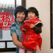 Chinese mother holding her daughter looking at camera smiling — Stock Photo