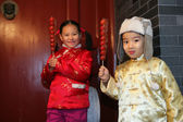 Two chinese children dressed in traditional clothing raising can — Stock Photo