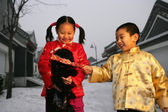 Two chinese children playing with a black dog — Stock Photo