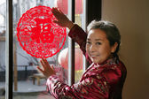 Chinese mature women posting a chinese cut paper on window — Stock Photo
