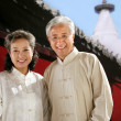 Stock Photo: Oriental senior couple beside temple