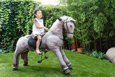 Girl riding toy horse — Stock Photo