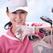Young woman holding golf clubs — Stock Photo