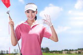 Young woman holding golf ball — Stock fotografie