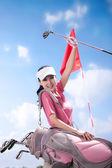 Mladá žena držení golfové hole — Stock fotografie