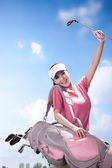 Woman carrying golf bag — ストック写真
