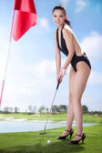 Sexy woman holding golf clubs — Stock Photo