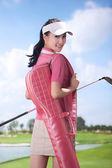 Woman carrying golf bag — Stock Photo