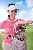 Ung kvinna anläggning golfklubbor — Stockfoto