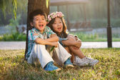 Boy and girl sitting on the ground — Stockfoto