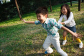Boy and girl playing outdoors — Stock Photo