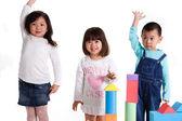 Menino e meninas jogando tijolos de brinquedo — Foto Stock