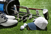 Golf shoes,hat,balls,tee and clubs in bag — Stock Photo