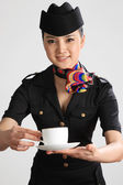 Chinese flight attendant holding a cup of coffee — Stock Photo
