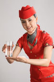 Chinese flight attendant holding cup of water — Stock Photo