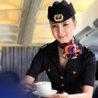 Flight attendant serving people on airplane — Stock Photo #37256687