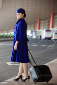 Chinese flight attendant pulling a suitcase — Stock Photo