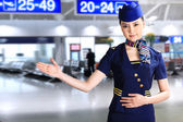 Flight attendant making hand gesture — Stock Photo