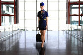 Flight attendant carrying her luggage — Stock Photo