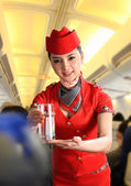 Flight attendant serving people on airplane — Stock Photo