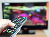 Hand pointing a tv remote control towards the television — Stock Photo