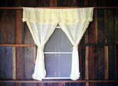 White drape and old wooden window — Stock Photo