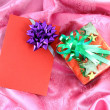 Gift box and card on pink satin — Stock Photo
