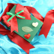 Green gift box with red ribbon on blue satin — Stock Photo