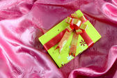 Yellow gift box with ribbon on pink satin — Stock Photo