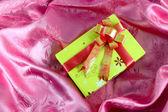 Yellow gift box with ribbon on pink satin — Stock Photo