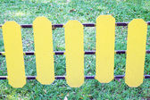 Yellow wooden fence on a green meadow — Stockfoto