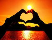 Hart vorm met man en vrouw handen op de zon gemaakt — Stockfoto