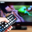 Hand pointing tv remote control towards television — Stockfoto #26422291