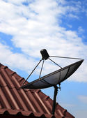 Black satellite dish on house roof — Stock Photo