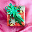 Red gift box with green ribbon on pink satin — Stock Photo