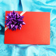 Red gift card with ribbon on blue satin — Stockfoto