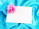 Gift card with ribbon on blue satin — Stock Photo