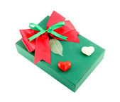 Green gift box with red ribbon on white background — ストック写真