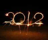 The boy write 2012 new year (fires) — Stock Photo