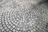 Closeup view on a cobblestone road - circle pattern - background — Stock Photo