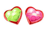 Wrapped red chocolate hearts on white background — Stock Photo