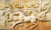 Stone sculpture van paard op de muur — Stockfoto